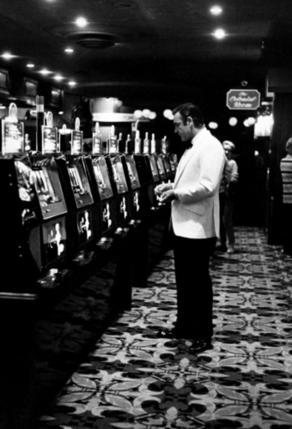 Terry O'Neill: Sean Connery at the Slots Las Vegas, 1971 Gelatin silver print, printed later Signed on recto Signed and numbered on verso 40 x 50 cm Editioned