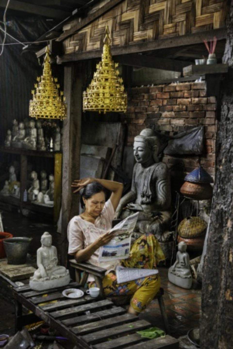 Steve McCurry: A Woman reads a Newspaper in her Shop Burma, 2013