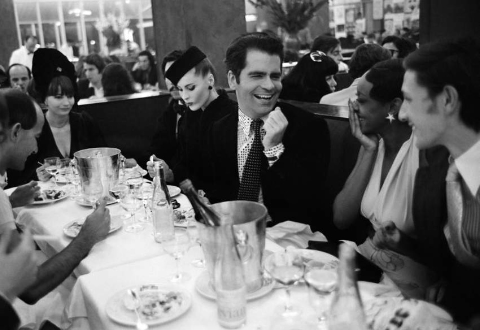 Max Scheler. Karl Lagerfeld has a laugh with model Amina Warsuma at La Coupole, Paris, 1972