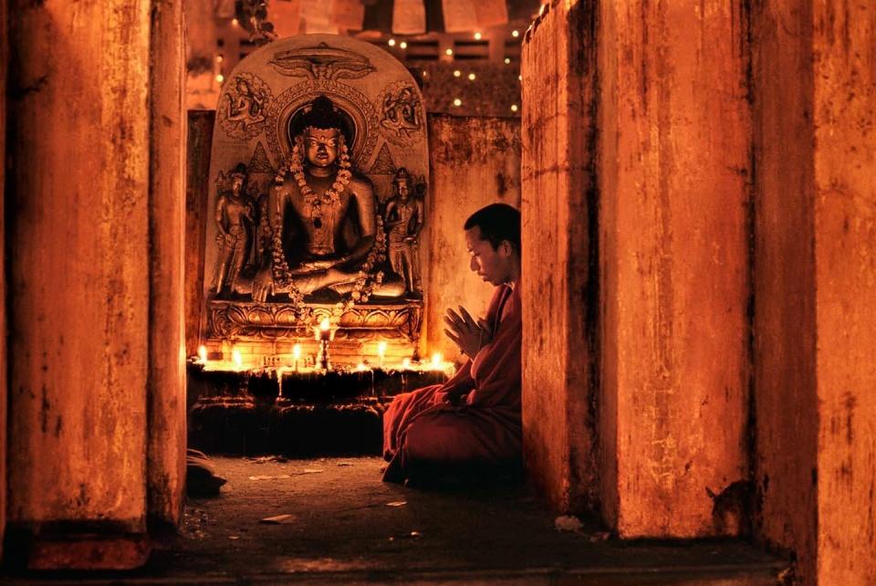 Steve McCurry. Monk prays at Bodh Gaya India, 2000