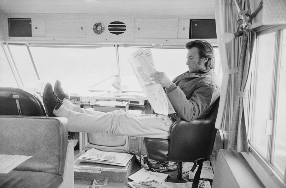 Terry O'Neill. Actor Clint Eastwood reading a newspaper in a mobile home between takes.