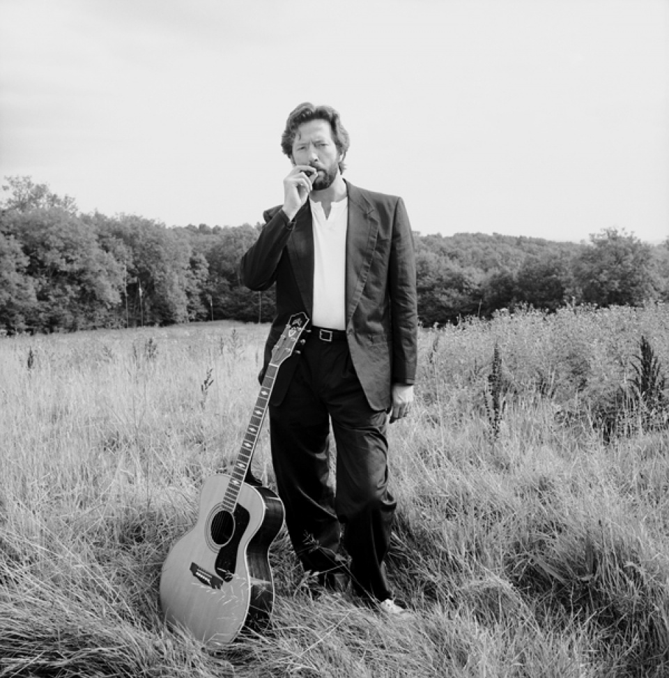 Terry O'Neill. Guitarist Eric Clapton in a field of long grass with his guitar, Surrey, 1993.